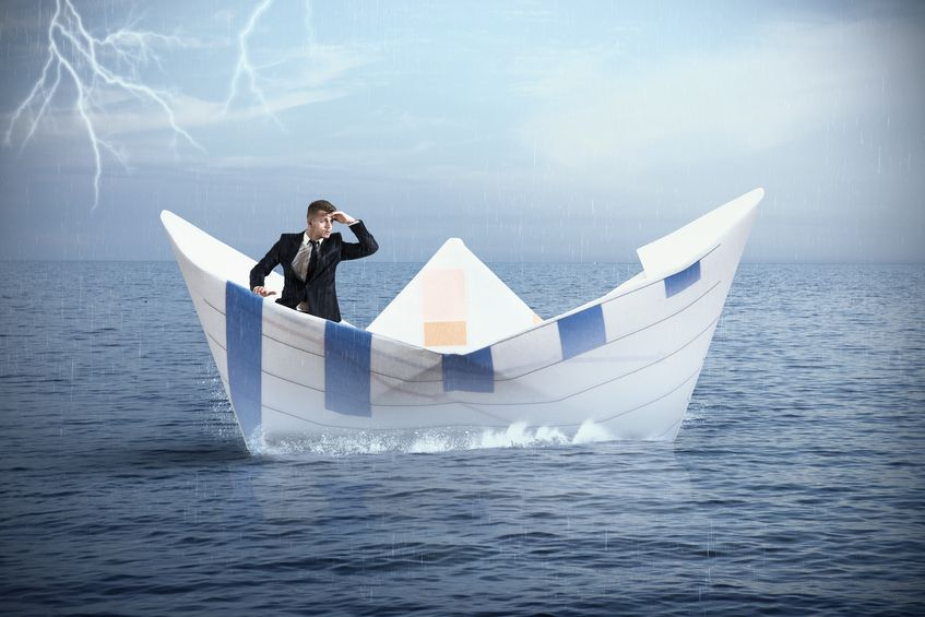 21509723-businessman-escapes-from-the-crisis-on-a-paper-boat